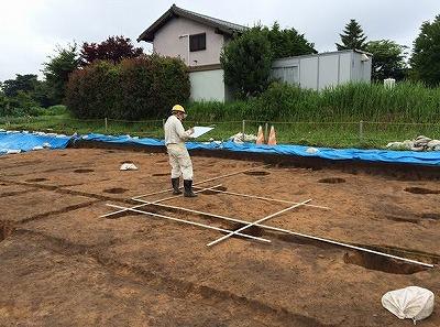 間竿を使用して掘立柱建物の記録をする奈文研職員.jpg